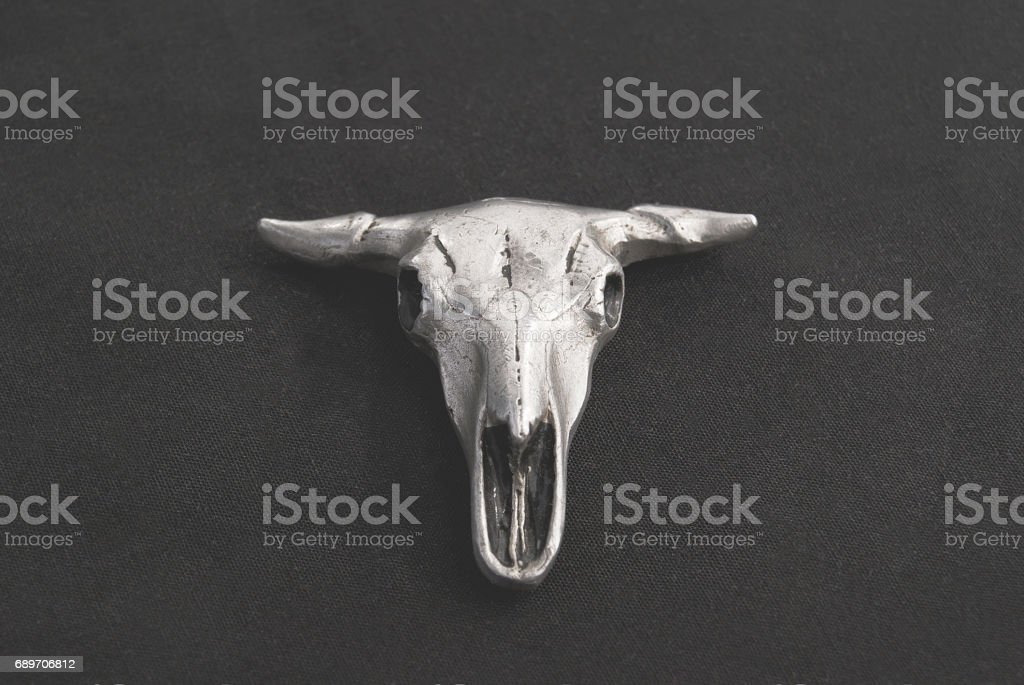 Pendant in the form of a bull's skull on a black background. stock photo