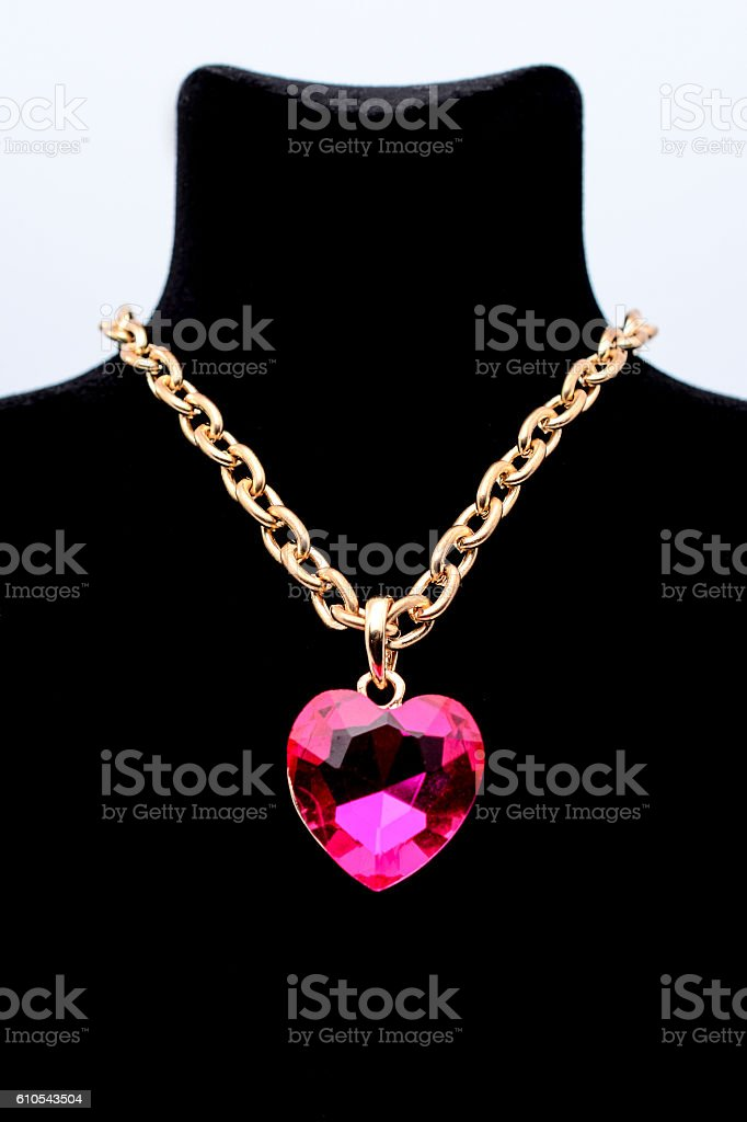 pendant with pink heart on a mannequin isolated on white stock photo