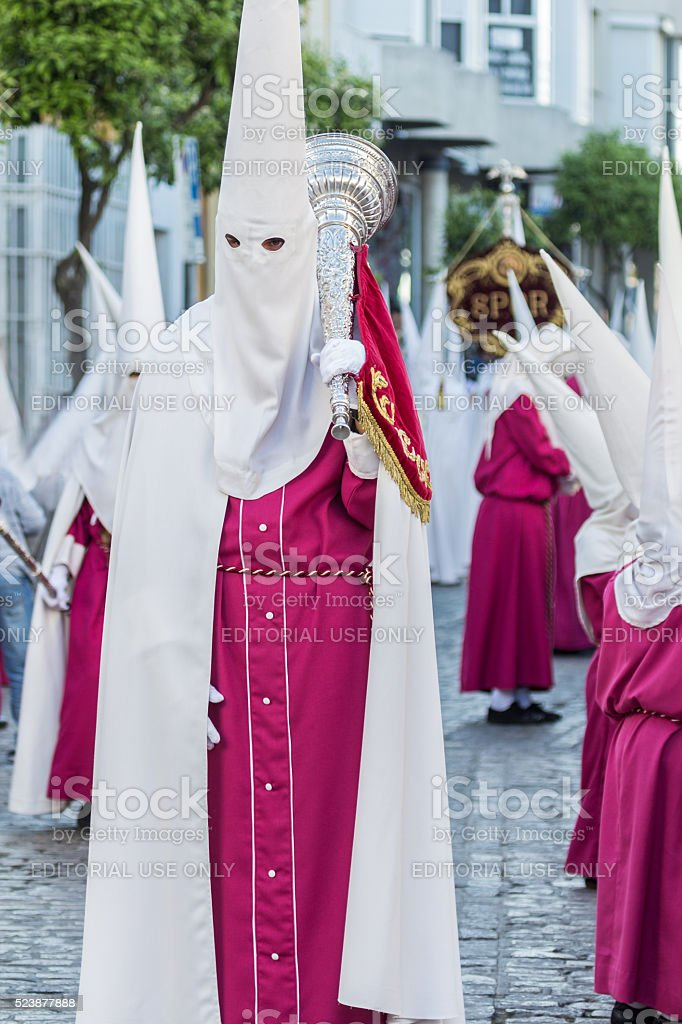 Penitent in white tunic holding a trumpet stock photo