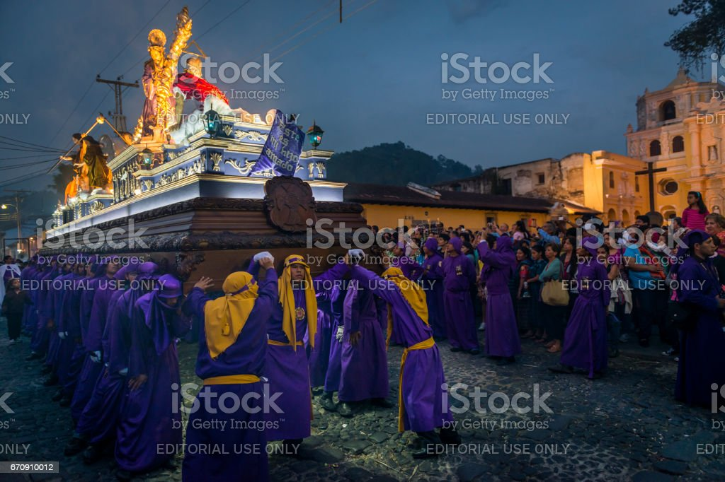 Penitents carrying a float with the image of Jesus Christ in an Easter procession at night during the Holy Week in Antigua, Guatemala stock photo