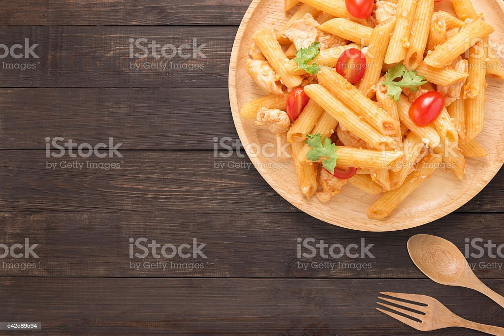 Penne pasta in tomato sauce with chicken on a table. stock photo