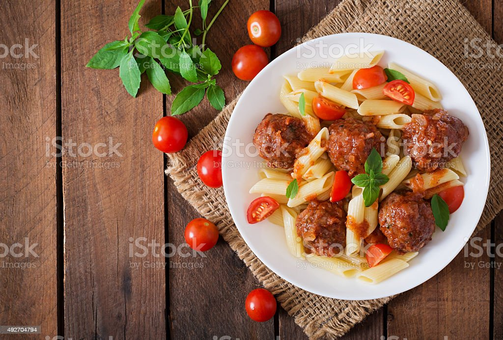 Penne pasta with meatballs in tomato sauce stock photo