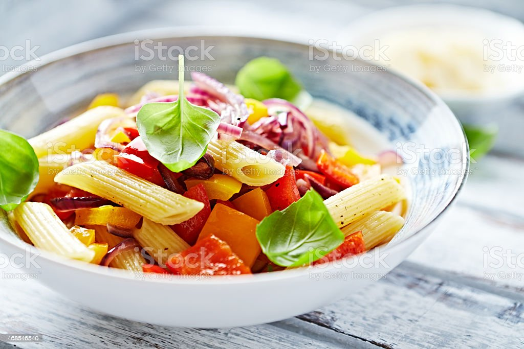 Penne pasta with peppers and basil stock photo