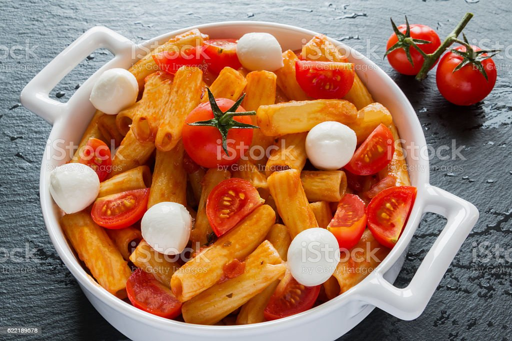 Penne pasta with sauce, mozzarella cheese and cherry tomatoes stock photo