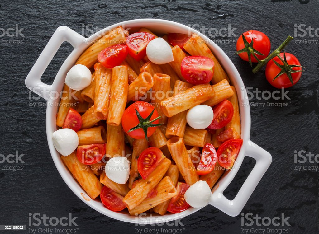 Penne pasta with sauce, mozzarella cheese, tomatoes, top view stock photo