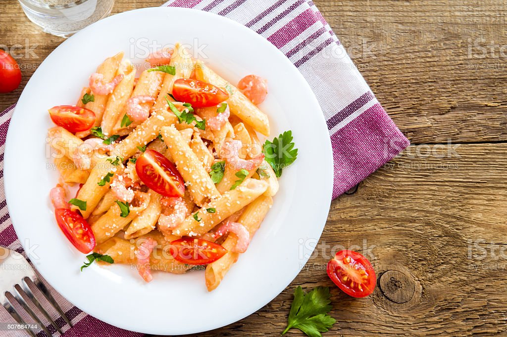 Penne pasta with shrimps, tomato sauce stock photo