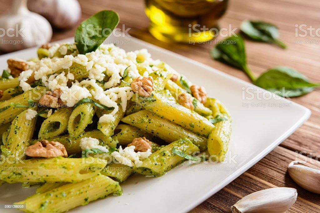 Penne pasta with spinach pesto, walnuts and mozzarella stock photo