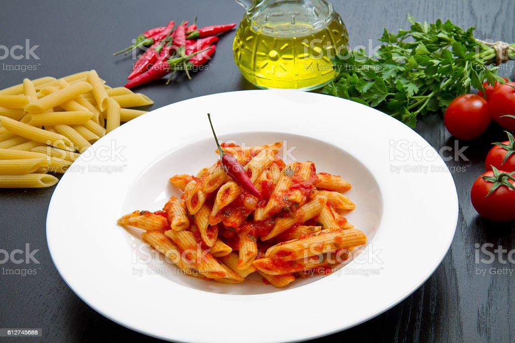 penne with arrabbiata sauce and fresh ingredients stock photo