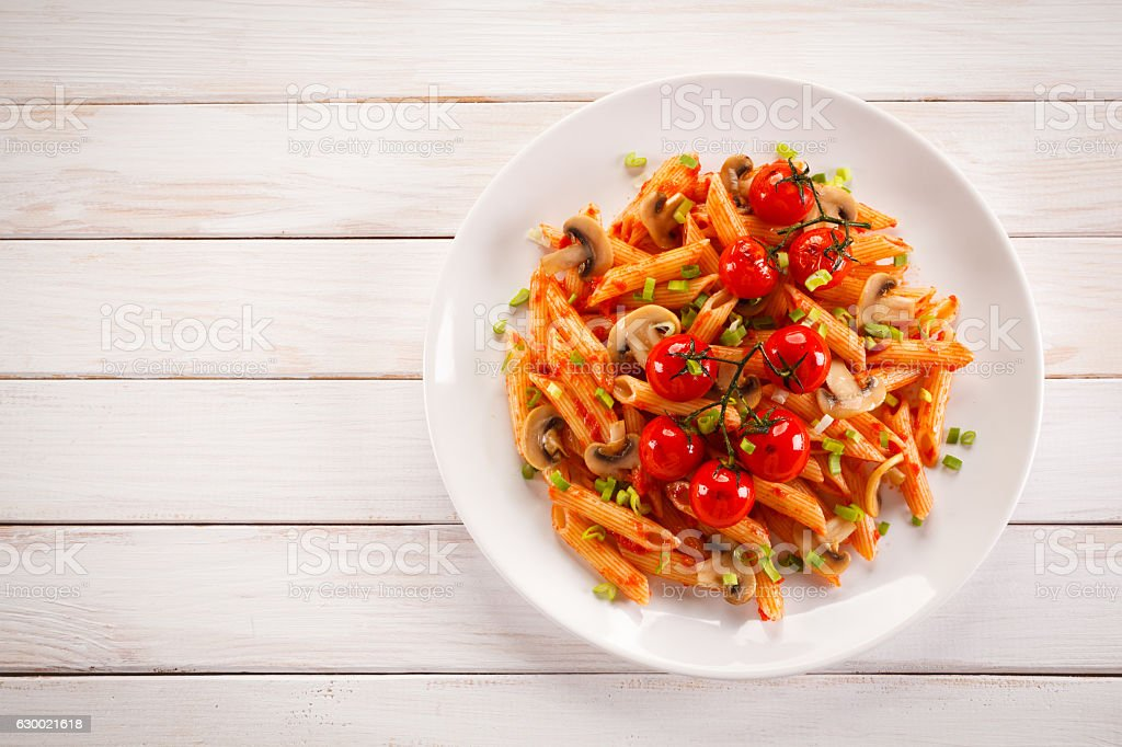 Penne with pesto sauce and vegetables stock photo