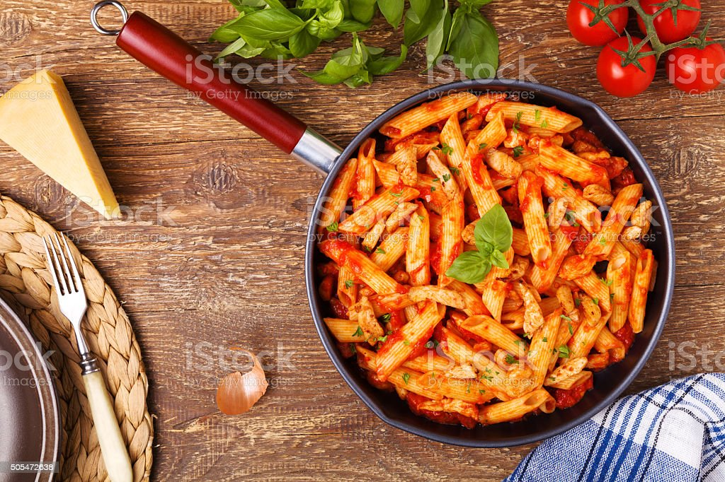 Penne with roasted chicken in tomato sauce stock photo