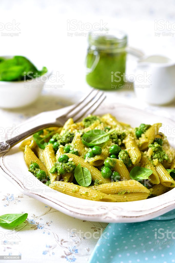 Penne with spinach pesto and green pea. stock photo