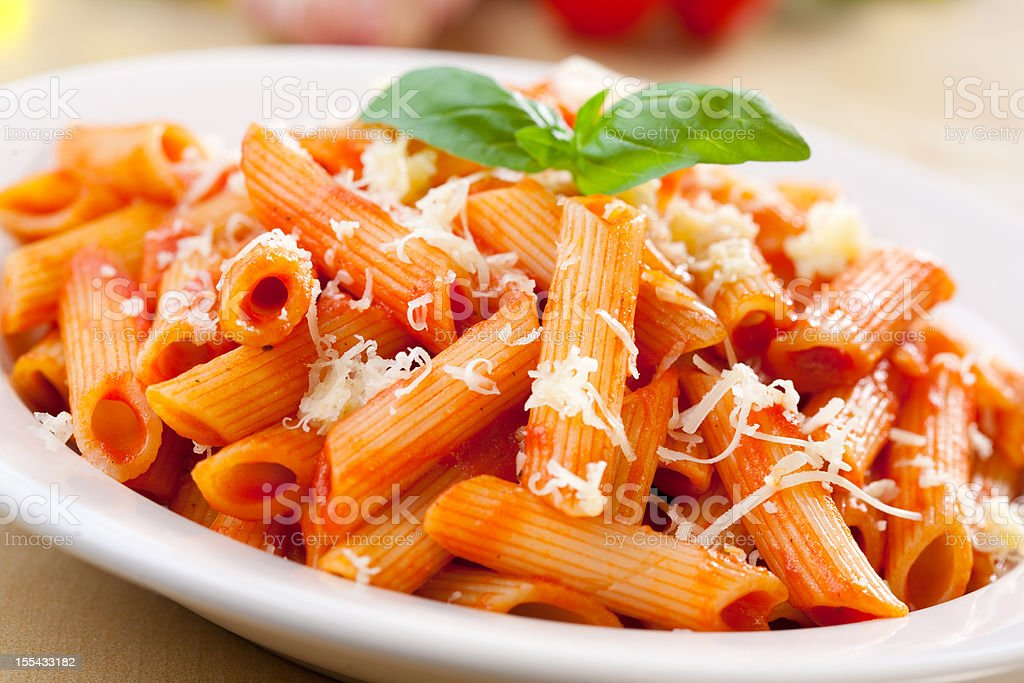 Penne with tomato sauce, basil and cheese on top stock photo