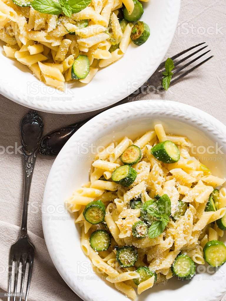 Pennette pasta with zucchini, mint leaves and parmesan stock photo