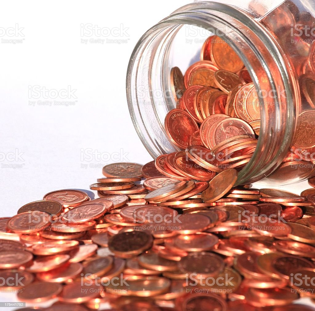 Pennies pouring out of glass jar on white background  royalty-free stock photo