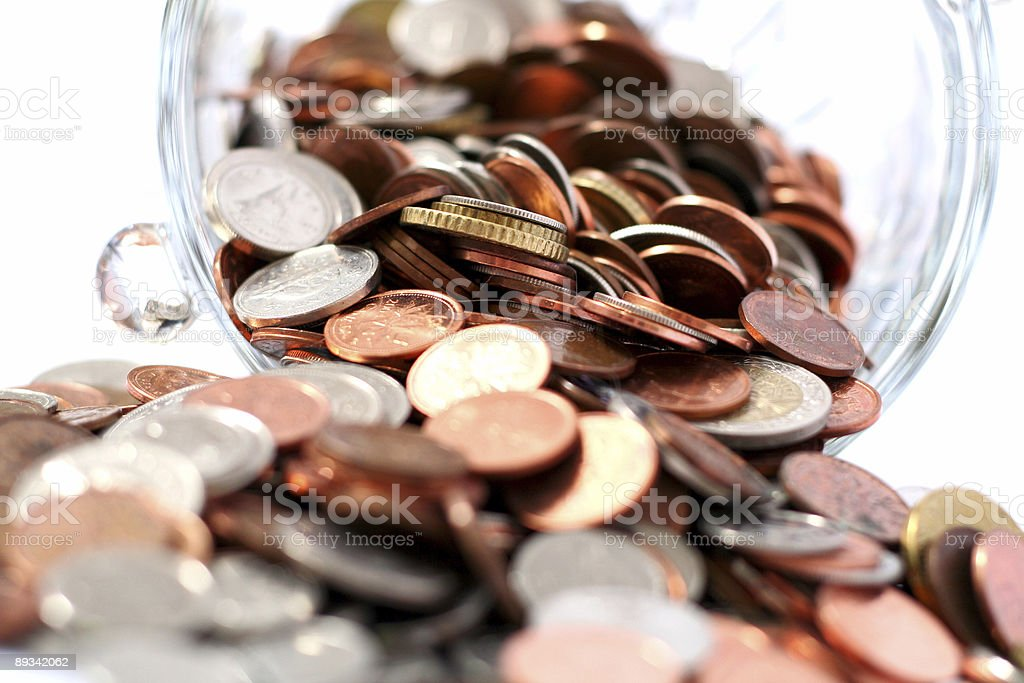 Pennies spilling out of a jar stock photo
