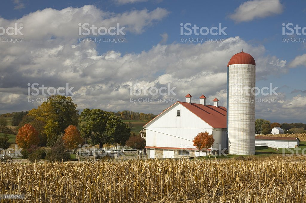 Pennsylvania Red roof barn and silo with autumn colored trees stock photo