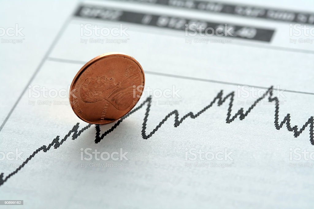 Penny on its side resting on a stock fluctuation chart stock photo