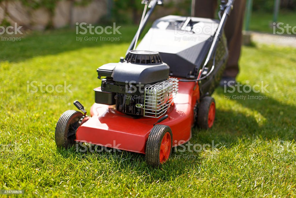Pensioner mowing lawn with machine stock photo