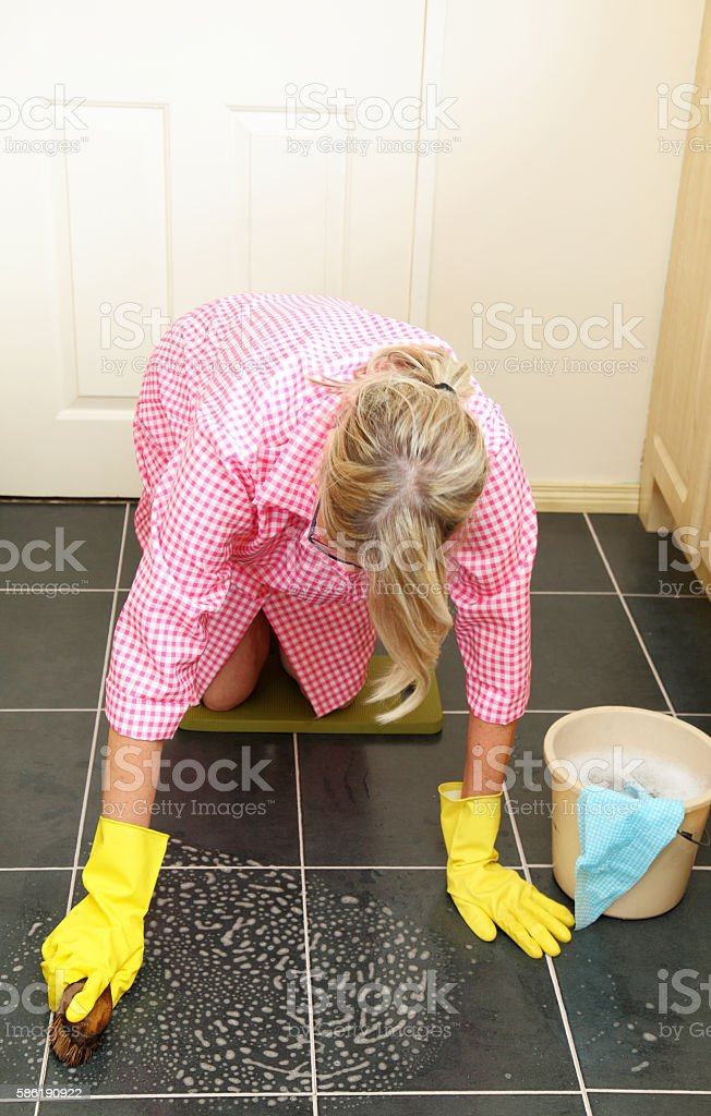 pensioner on her knees scrubbing the kitchen floor stock photo