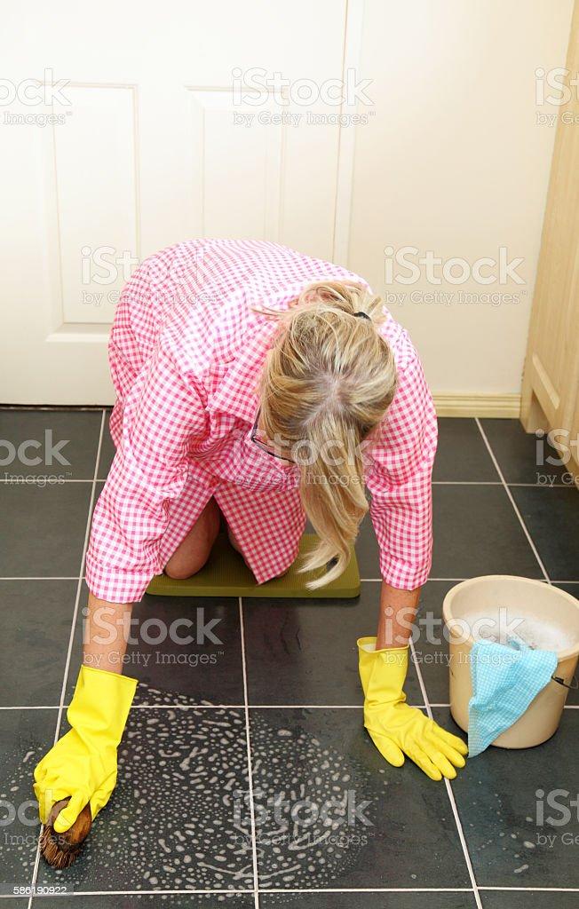 pensioner on her knees scrubbing the kitchen floor stock photo