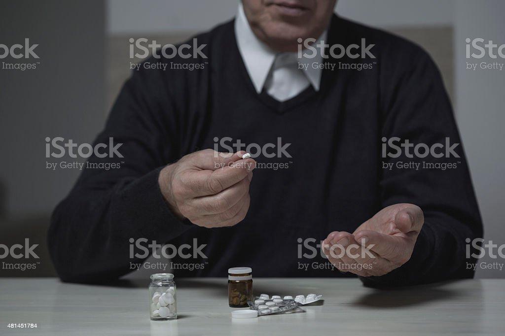 Pensioner taking pills stock photo