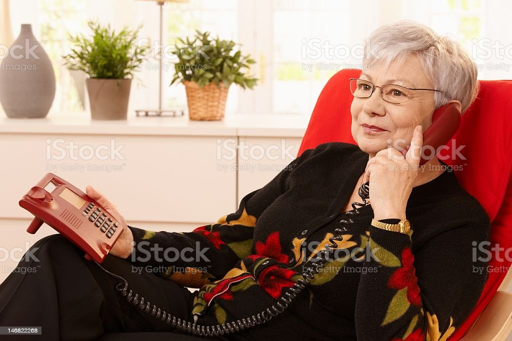 Pensioner woman using landline phone stock photo