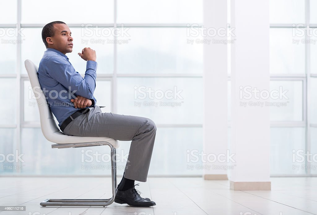 Pensive African American businessman sitting on chair. stock photo