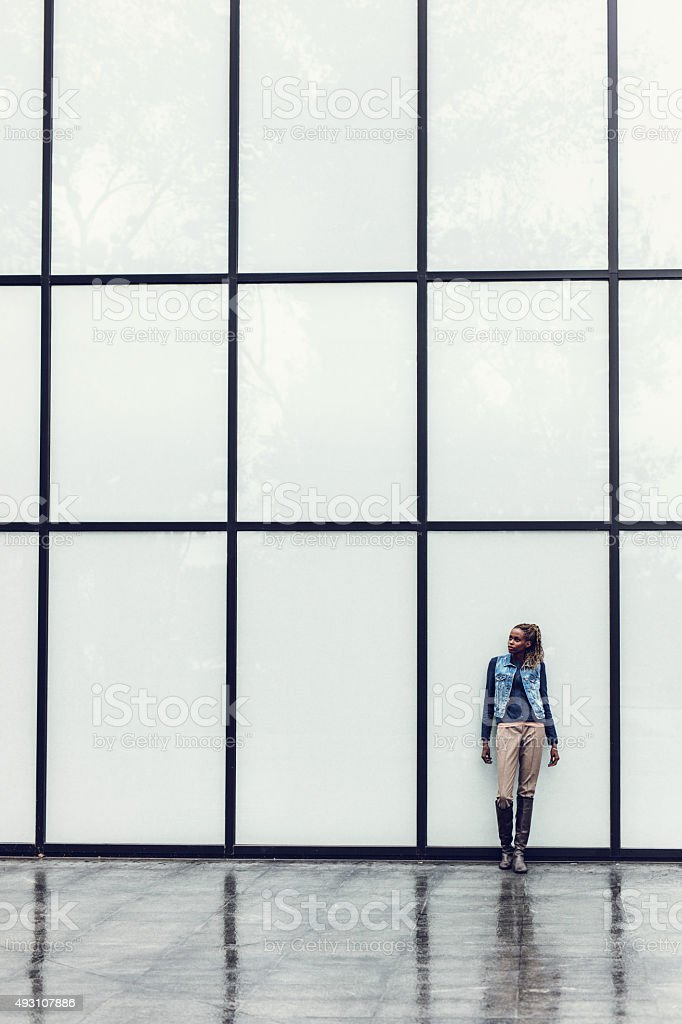 Pensive African American businesswoman against glass curtain wall. stock photo