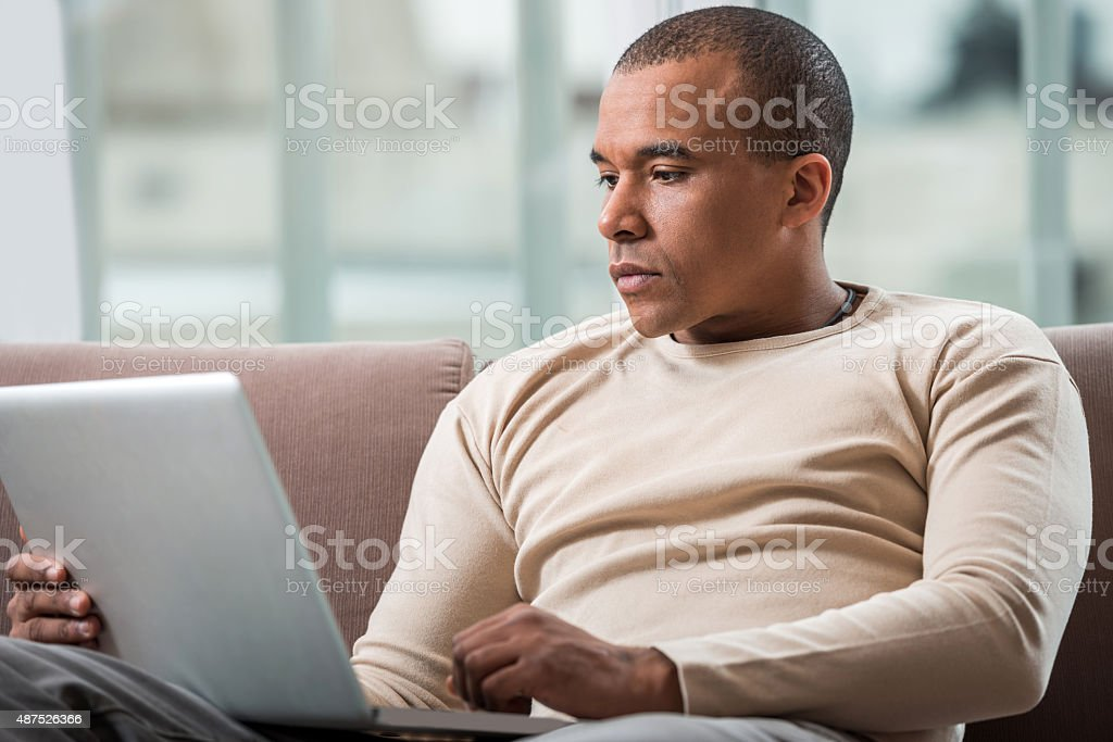 Pensive African American using laptop at home. stock photo