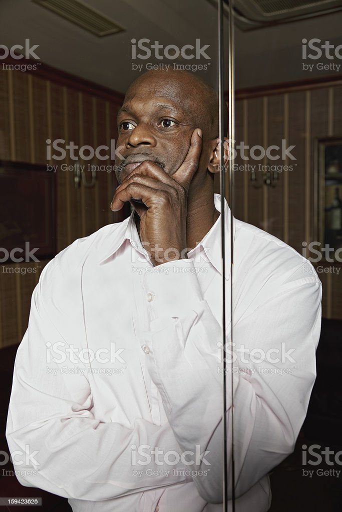 Pensive african man in a dark office royalty-free stock photo