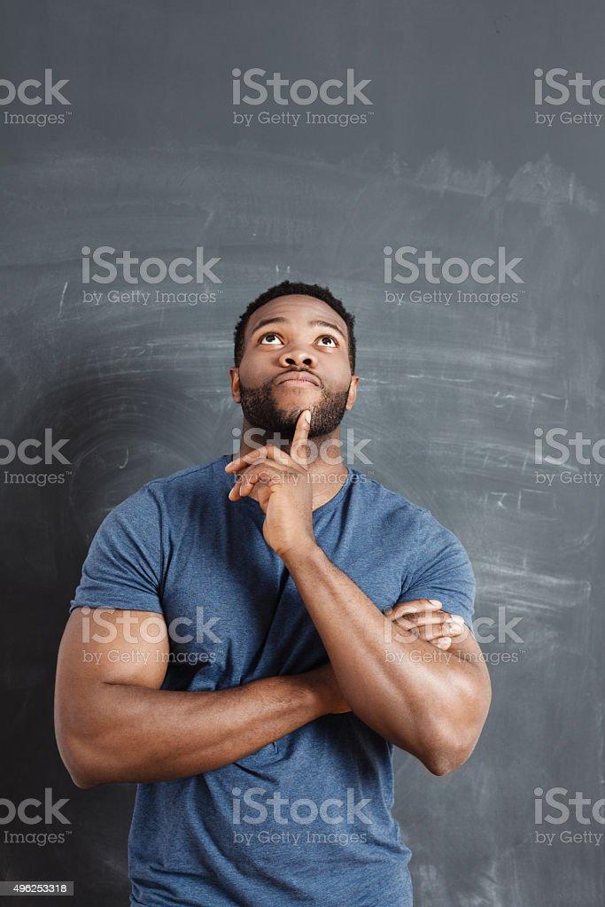 Pensive afro american man against blackboard stock photo