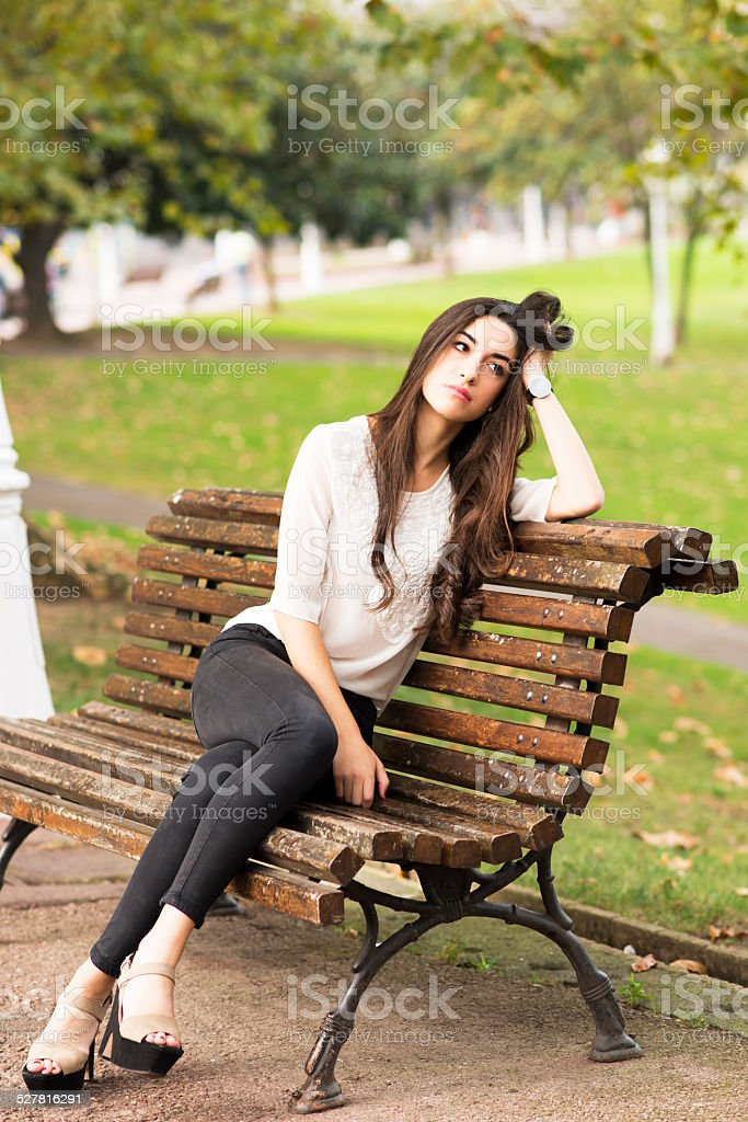 Pensive and elegant beautiful woman sitting on old bench. stock photo