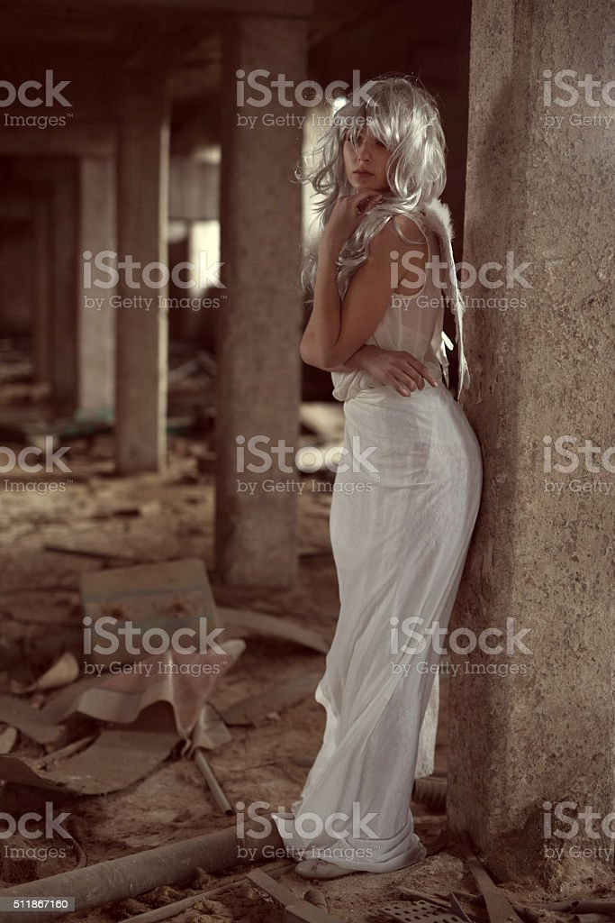 Pensive angel in a ruin looking away. stock photo