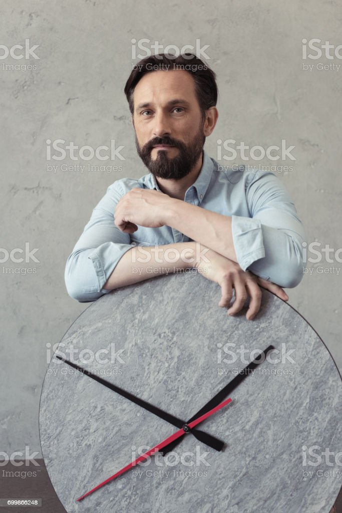 pensive bearded man leaning on clock and looking at camera stock photo