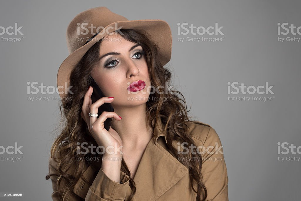 Pensive beauty wearing hat talking on the phone looking away stock photo