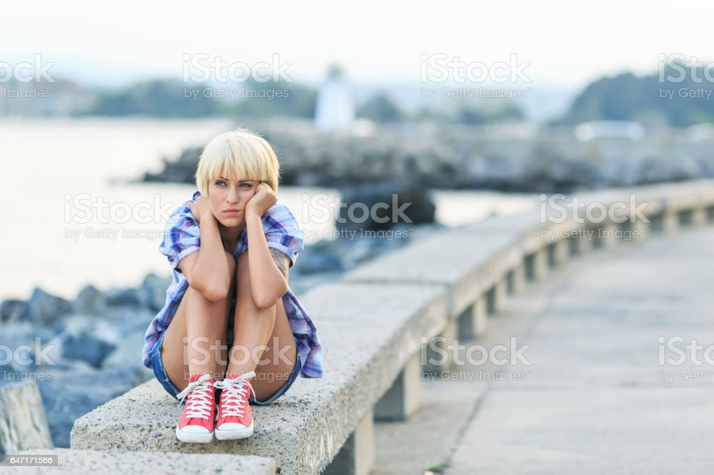 Pensive blond woman sitting on beach stock photo