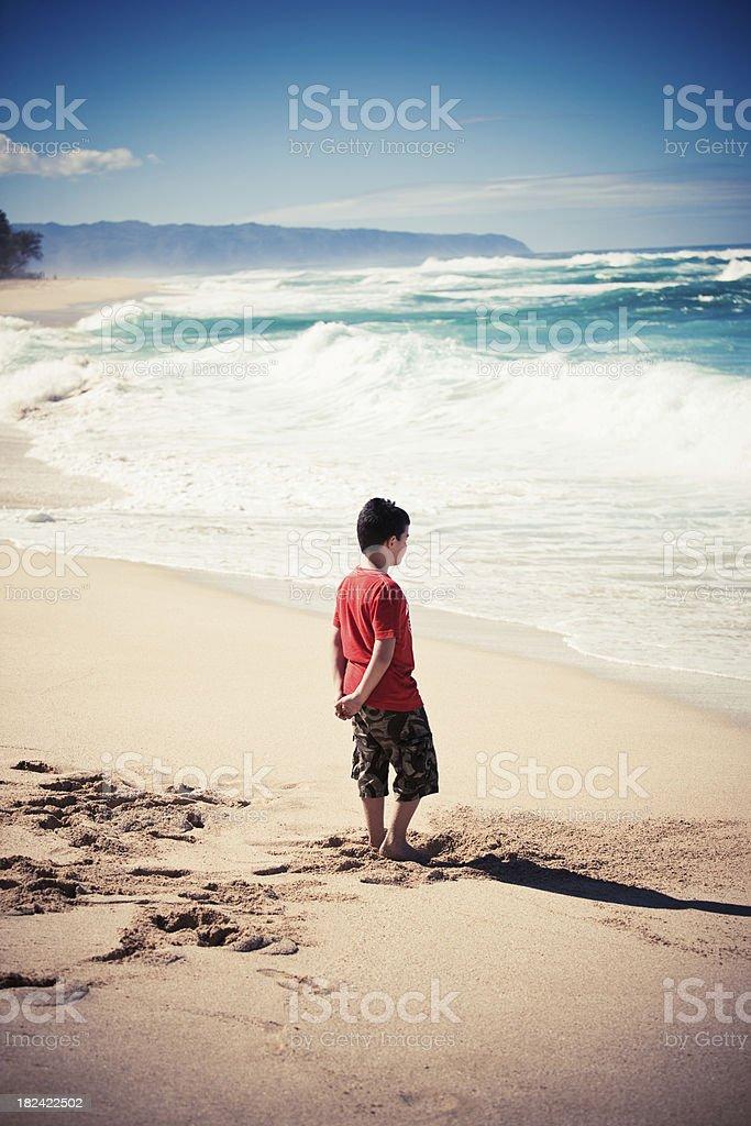 Pensive boy at the Beach - Hawaiian Waves royalty-free stock photo