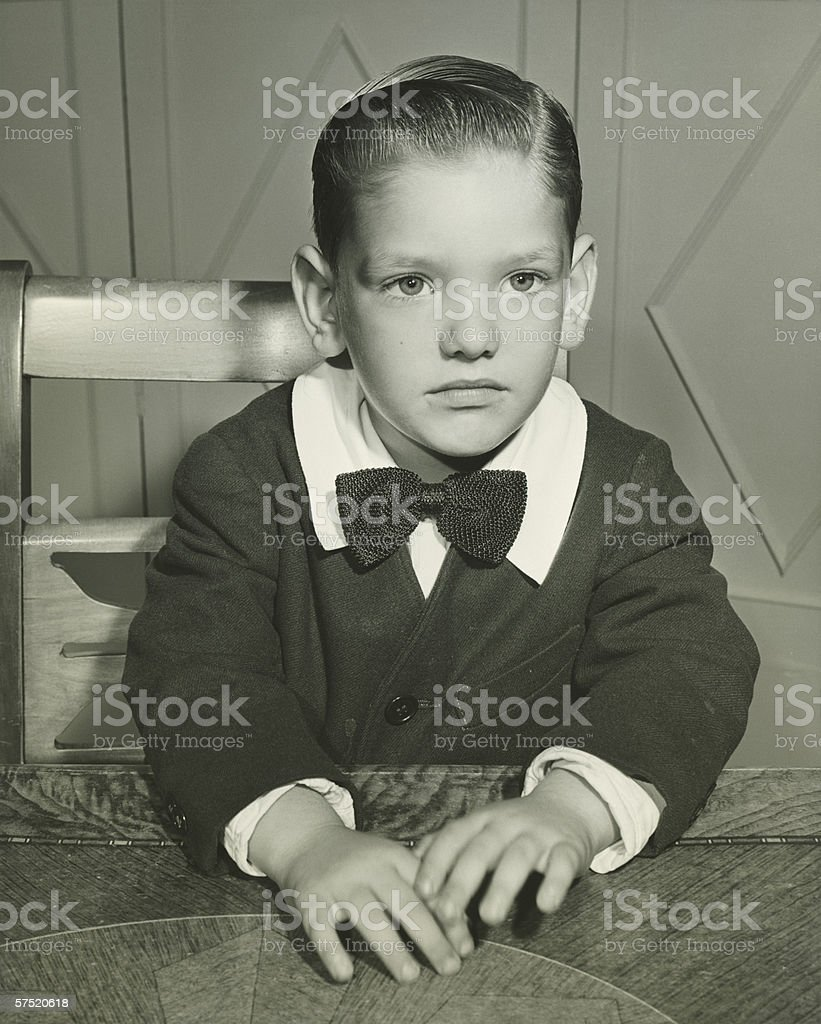 Pensive boy (4-5) posing at table, (B&W), portrait stock photo
