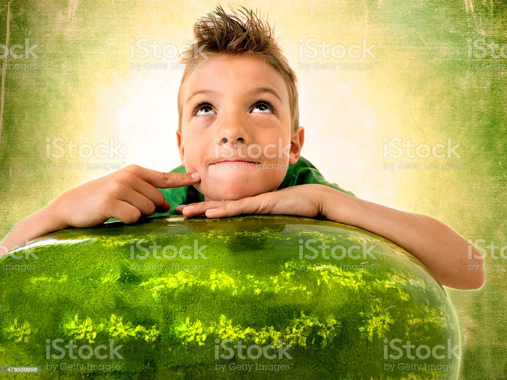 pensive boy resting on a giant watermelon stock photo