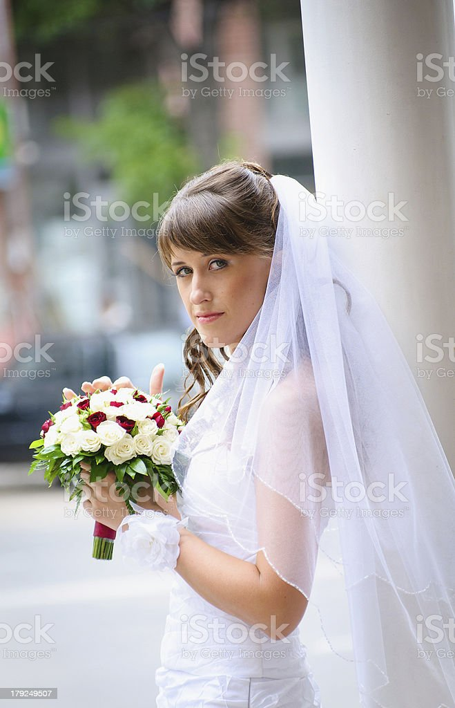 pensive bride in white dress standing and holding roses bouquet royalty-free stock photo