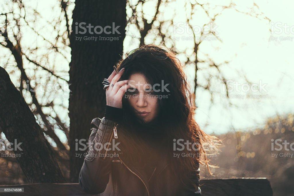 Pensive brunette smoking cigarette in a park stock photo