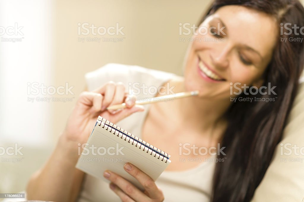 Pensive brunette woman writing to notebook royalty-free stock photo