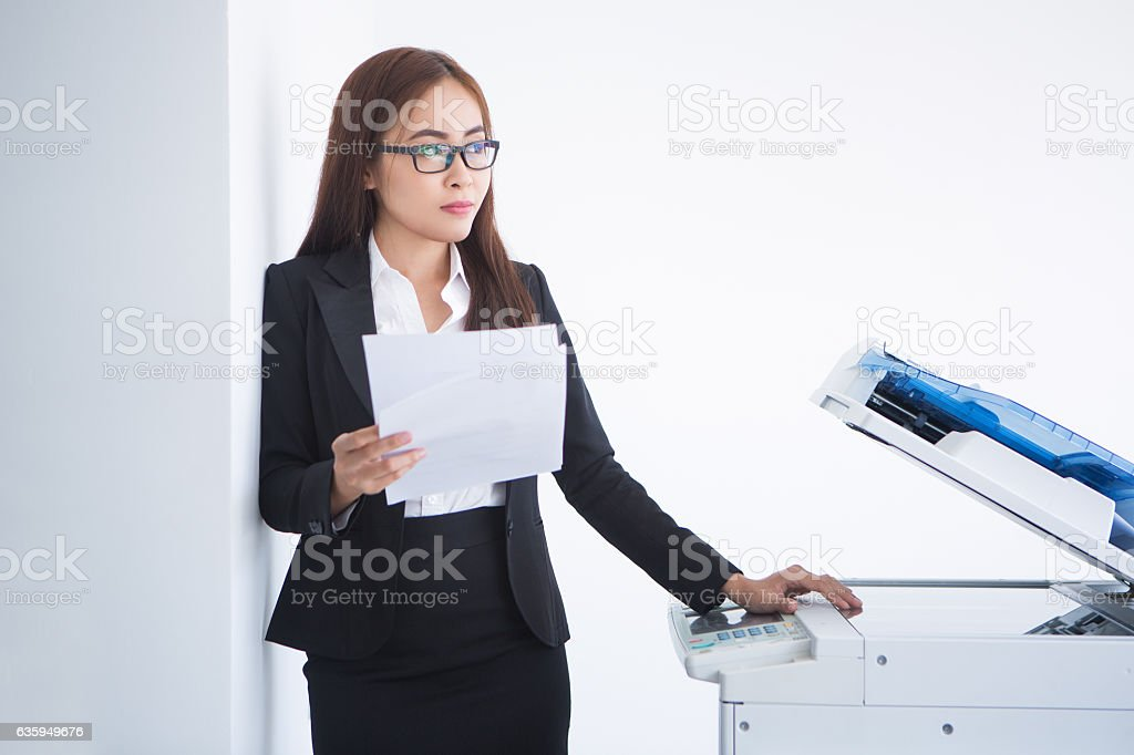 Pensive Business Woman at Copier with Document stock photo