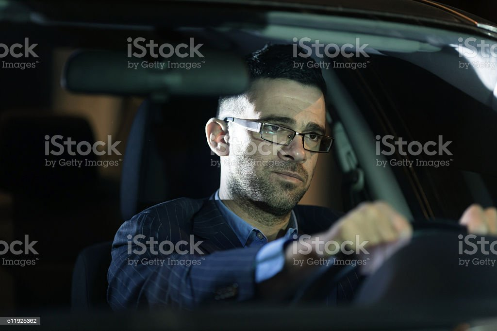 Pensive businessman driving his car by night stock photo