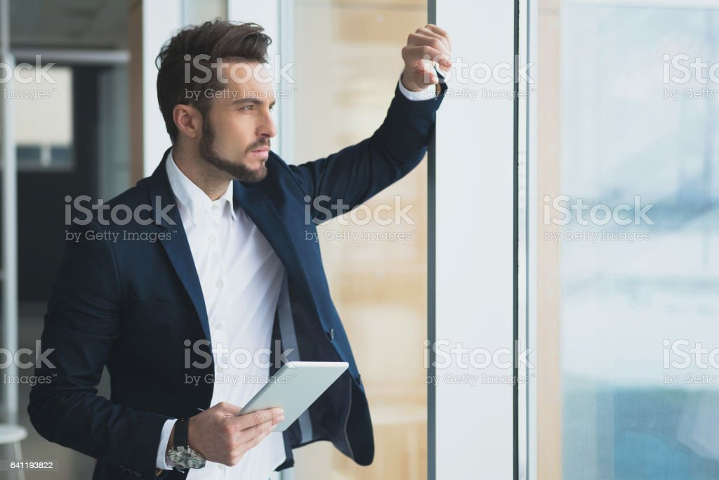 Pensive businessman holding tablet, thinking about new project. stock photo