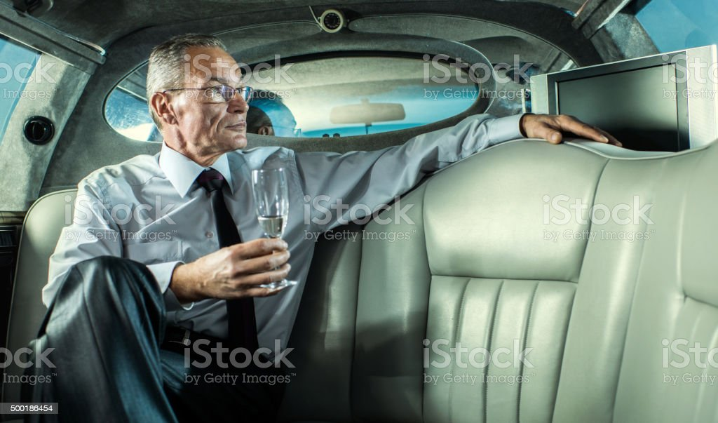 Pensive businessman in a limousine with glass of champagne. stock photo