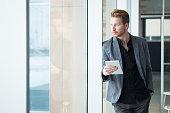 Pensive businessman leaning against window  holding digital tablet.