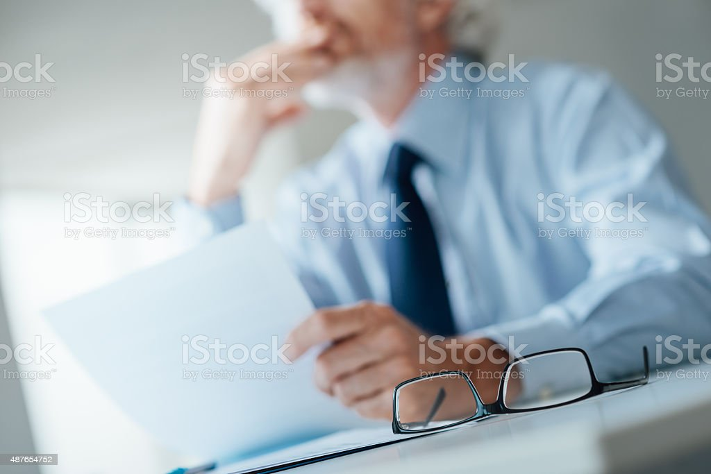 Pensive businessman reading a contract stock photo