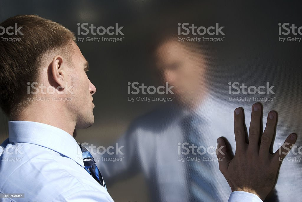 Pensive Businessman Stands Touching Reflection stock photo