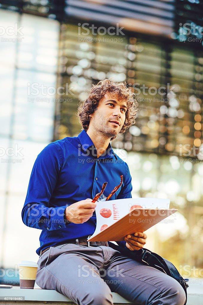 Pensive businessman using coffee break for data analysis stock photo